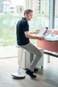 Mann sitzt lächelnd auf dem Steh-Sitz se:fit vor seinem hochgefahrenen Schreibtisch.