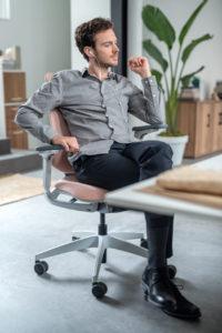 Mann mit Kopfhörern sitzt auf dem se:flex Bürodrehstuhl.