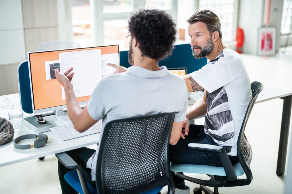 Zwei Männer unterhalten sich am Arbeitsplatz auf se:motion Drehstühlen sitzend.